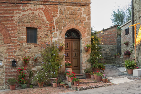 pienza: Montichiello - Italy, October 29, 2016: Quiet street in Montichiello, Tuscany with typical shuttered windows and paved streets. Monticchiello is the only fraction of the municipality of Pienza, in the province of Siena. It is a typical medieval village im