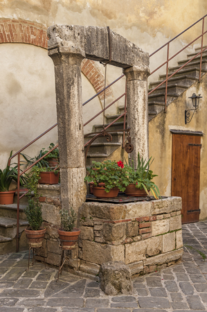 picturesque: SAN QUIRICO DORCIA, ITALY - OCTOBER 30, 2016 - Picturesque traditional Italian courtyard in the center of San Quirico dOrcia, Val dOrcia, Tuscany, Italy Editorial