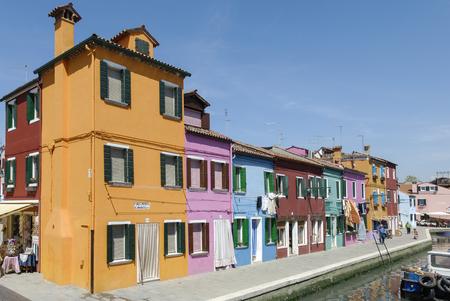 BURANO - ITALIË, 18 APRIL, 2009: Panorama's van kleurrijke gebouwen, niet geïdentificeerde mensen en boten voor een kanaal in Burano, een verfijnd klein stadshoogtepunt van kanalen dichtbij Venetië. Gelegen in de regio Veneto, Noord-Italië