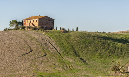 unesco: VAL DORCIA, TUSCANY-ITALY, OCTOBER 30, 2016: Farmhouse in the scenic Tuscan landscape with rolling hills and valleys in Val DOrcia, Italy