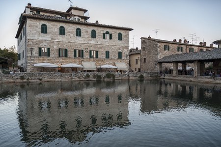 BAGNO VIGNONI, TUSCANY ITALY - October 30, 2016:  people in the old thermal baths in the medieval village of Bagno Vignoni, Tuscany, Italy - Spa basin in the ancient Italian town. 에디토리얼