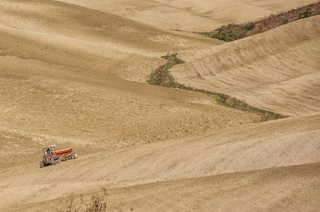 st: SAN QUIRICO DORCIA, TUSCANY  ITALY - OCTOBER 31, 2016: Undefined farmer on a tractor in the beautiful tuscan landscape near San Quirico dOrcia with rolling hills in autumn. Located in Val DOrcia countryside - Italy. Stock Photo
