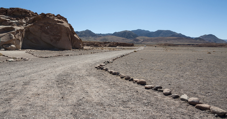 Unpaved road near Ancient Petroglyphs on the Rocks at Yerbas Buenas in the Atacama Desert in Chile