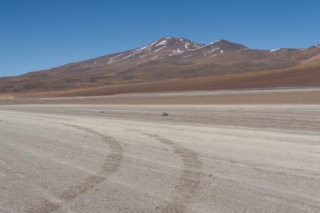 Unpaved Road in the Altiplano of the Siloli desert, part of the Reserva Eduardo Avaroa, Bolivia - at an altitude of 4600m near the border of Chile and the Atacama desert, South America Imagens