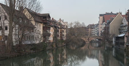 Houses and a bridge reflected in a river in the old town of Nuremberg seen from Henkersteg covered bridge across Pegnitz river - Germany