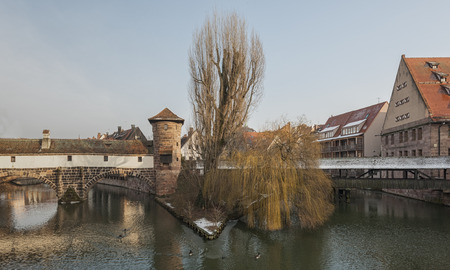 the famous Former Wine Depot (Weinstadel) and Water Tower (Wasserturm) over the river Pegnitz and Henkersteg and Henkerhaus seen from Maxbrcke - Nuremberg, Germany