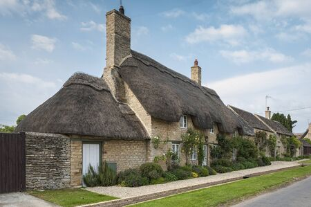 Narrow lane with romantic thatched houses and stone cottages in the lovely Minster Lovell village, Cotswolds, Oxfordshire, England Zdjęcie Seryjne