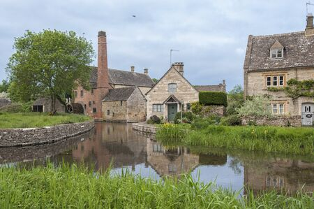 LOWER SLAUGHTER, COTSWOLDS, GLOUCESTERSHIRE, ENGLAND - MAY, 27 2018: The Old Mill along the River Eye in the lovely village of Lower Slaughter, Cotswolds, Gloucestershire, England, UK Editorial