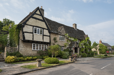 Narrow lane with romantic thatched houses and stone cottages in the lovely Minster Lovell village, Cotswolds, Oxfordshire, England