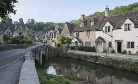 CASTLE COMBE, COTSWOLDS, UK - MAY 26, 2018: Street view of old riverside cottages in the picturesque Castle Combe Village, Cotswolds, Wiltshire, England - UK Publikacyjne