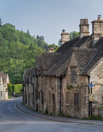 CASTLE COMBE, COTSWOLDS, UK - MAY 26, 2018: Typical and picturesque English countryside cottages in Castle Combe Village, Cotswolds, Wiltshire, England - UK Publikacyjne
