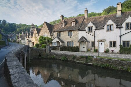 CASTLE COMBE, COTSWOLDS, Royaume-Uni - 26 MAI 2018 : vue sur la rue de vieux cottages au bord de la rivière dans le pittoresque village de Castle Combe, Cotswolds, Wiltshire, Angleterre - Royaume-Uni