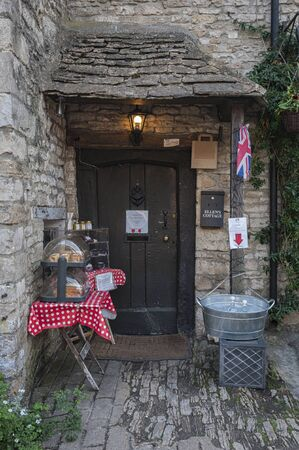CASTLE COMBE, COTSWOLDS, UK - MAY 26, 2018: Beautiful front of old stone cottage with set up table selling home made cakes in the picturesque Castle Combe Village, Chippenham, Cotswolds