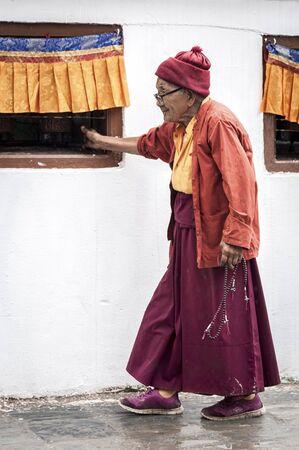Kathmandu, Nepal-August, 13 2018: Unidentified Buddhist believers, mostly Tibetan exiles, turn clockwise around the Boudhanath stupa spinning the hundreds of prayer wheels