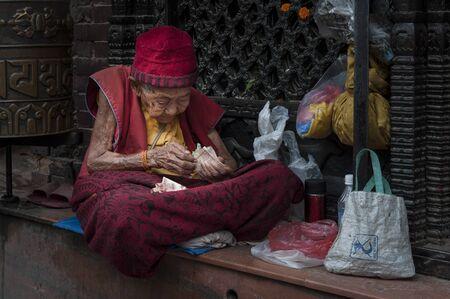 Kathmandu, Nepal-August, 13 2018: A 100-year-old Tibetan Buddhist nun sitting next to a prayer wheel at the entrance to the Boudhanath stupa, Kathmandu