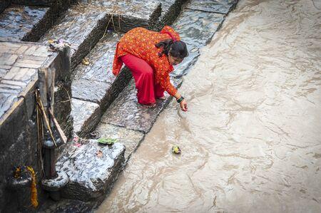 PASHUPATINATH, NEPAL - AUGUST 13, 2018: Unidentified devoted Hindu woman what is believed a holy bath in Bagmati river to wash away sins - at Pashupatinath Temple, a Hindu temple - Kathmandu, Nepal Publikacyjne
