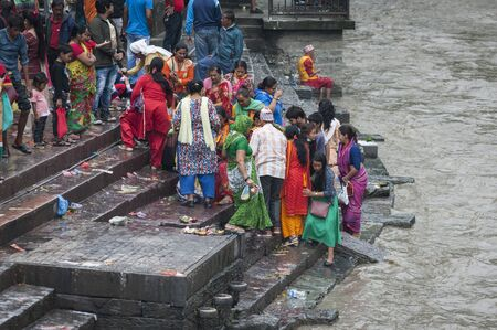 PASHUPATINATH, NEPAL - AUGUST 13, 2018: Unidentified indian people at an Hindu funeral at Pashupatinath Temple, a Hindu temple located on the banks of the Bagmati River. Kathmandu, Nepal