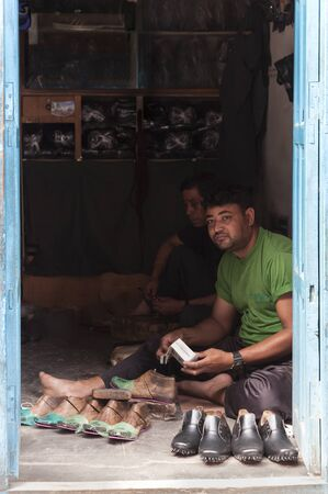 BHAKTAPUR, NEPAL AUGUST 13, 2018: Unidentified Nepalese Newari shoemakers in their shop in Bhaktapur