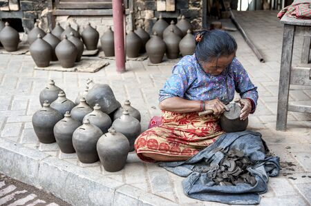 BHAKTAPUR, NEPAL AUGUST 13, 2018: Nepalese woman making pottery in Pottery square, a public square full of pottery wheels and rows of clay pots which are made by old fashioned way drying in the sun