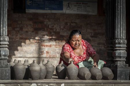 BHAKTAPUR, NEPAL? AUGUST 13, 2018: Nepalese woman making pottery in Pottery square, a public square full of pottery wheels and rows of clay pots which are made by old fashioned way drying in the sun