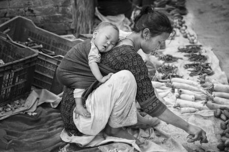 BHAKTAPUR, NEPAL AUGUST 13, 2018: Unidentified Nepalese woman with a little child selling vegetables in Bhaktapur