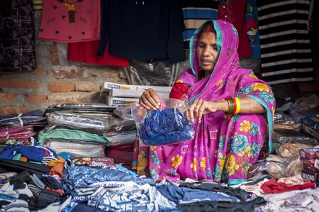 BHAKTAPUR, NEPAL AUGUST 13, 2018: Unidentified Nepalese woman selling clothes in Bhaktapur, Nepal
