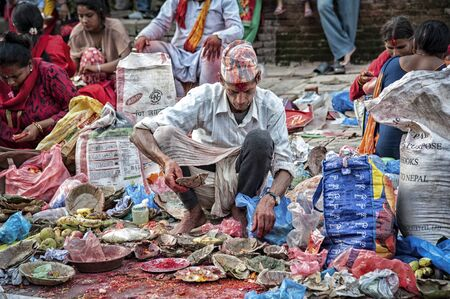 BHAKTAPUR, NEPAL AUGUST 13, 2018: Unidentified Nepalese Newari man selling vegetables and flowers in Bhaktapur