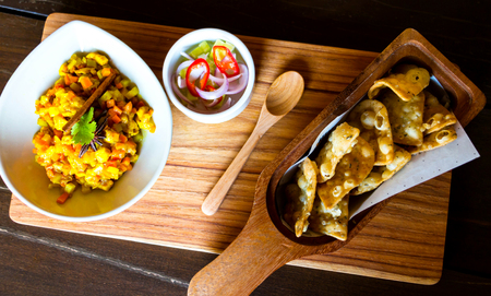 side dishes: curry puff new style served on wooden plate with side dishes