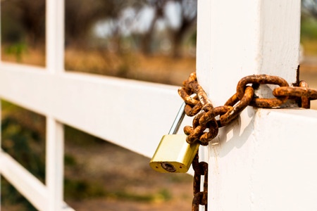secure site: chain locked white gate represent unallow to entry Stock Photo