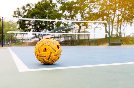 old sepak takraw ball in corner of old blue court