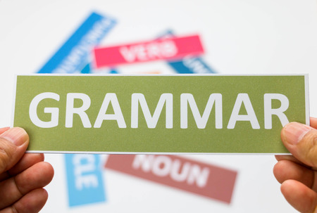 hand holding grammar english card over other colourful cards on white board represent active study english grammar Archivio Fotografico