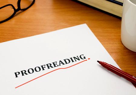 proeflezen woord op wit blad met rode pen, boeken, bril op houten tafel