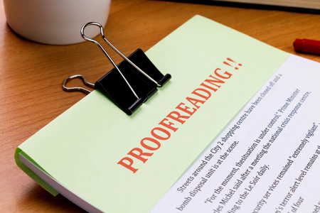 assay: proofreading red word on green sheet on wooden table represent proof read on document Stock Photo