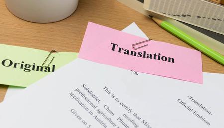 vertaling papier op houten tafel met boeken en mok Stockfoto