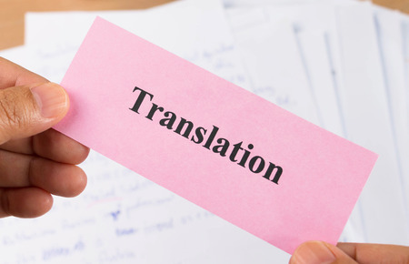 transcribe: hand holding translation pink card over blur document Stock Photo