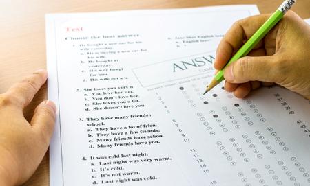 英語の質問や解答用紙の手でテーブルの上 写真素材
