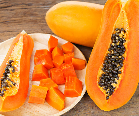 ripe cut papaya and slices on wooden table Stock Photo