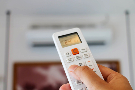 hand holding remote controller to adjust temperature Stock Photo