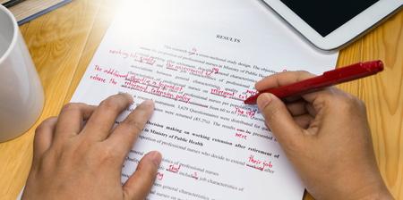 Mano che tiene penna rossa sopra testo di correzione di bozzetto sulla tabella Archivio Fotografico - 77900548