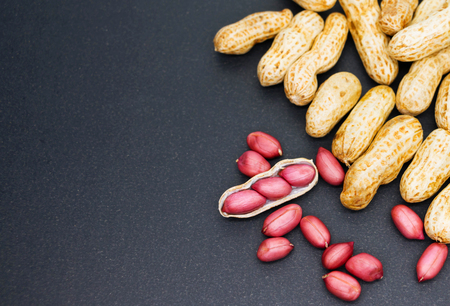 fresh red peanuts on black with copy space Stock Photo