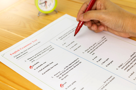 English grammar sheet on wooden desk
