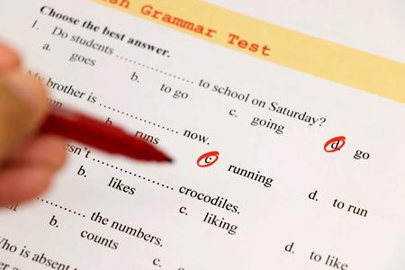 English grammar test sheet on wooden desk