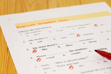 English grammar test sheet on wooden desk