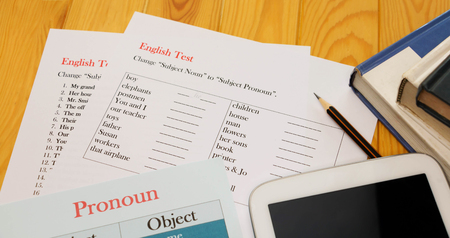 English test sheet on wooden desk represent school test in classroom