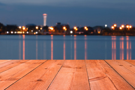 perspective wooden desk by blur lake at twilight