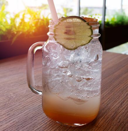 glass of ice lemonade on wooden table in restaurant