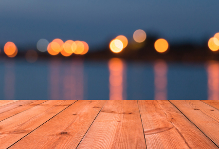 perspective wooden desk over blur light by lake Stock Photo