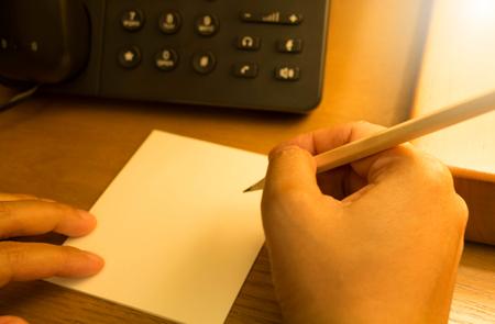 hand holding pencil writing on notepad Standard-Bild