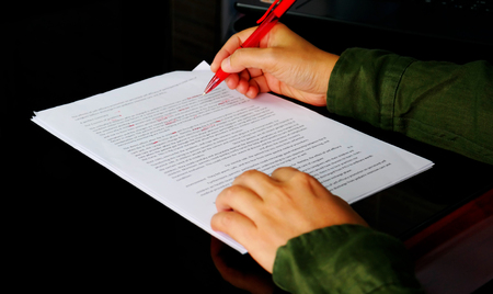 hand holding red pen to correct proofreading paper on black table in office Stock Photo
