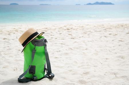 green water proof bag on white beach in island of Thailand  Standard-Bild